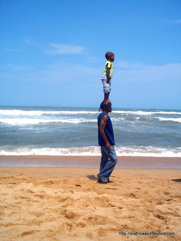 A child stands on a man's head at Umhlanga Beach