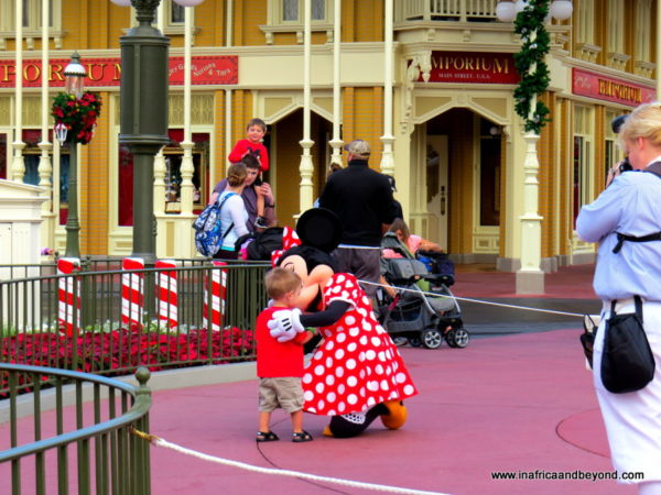 Minnie Mouse embraces a toddler